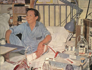 Man in hospital bed with machinery